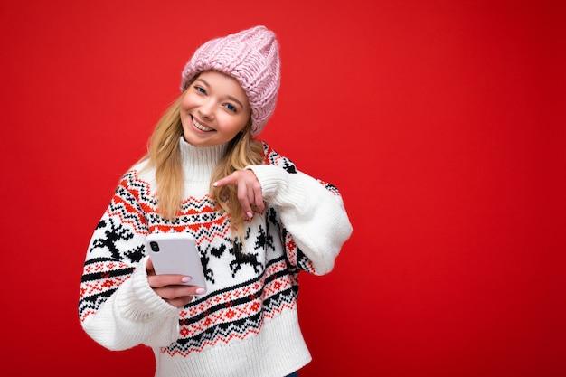 Foto de uma jovem sorridente atraente, positiva e bonita, vestindo uma roupa casual elegante