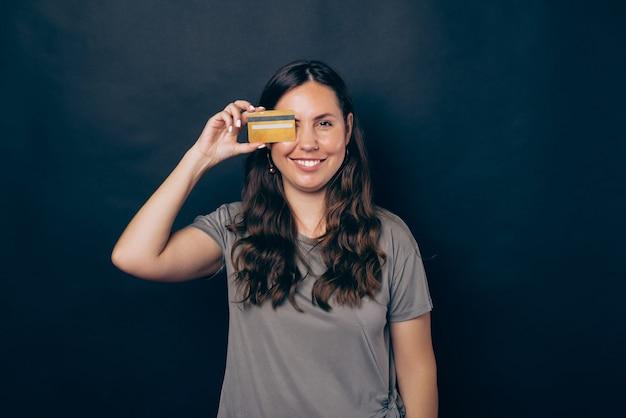Foto de uma jovem sorridente cobrindo os olhos com um cartão de crédito amarelo