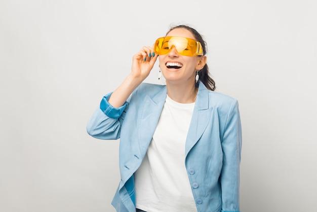 Foto de uma jovem sorridente e alegre com roupa formal, óculos grandes e amarelos, uma jovem engraçada