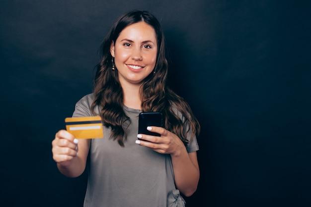 Foto de uma jovem sorridente, mostrando um cartão de crédito amarelo e usando o smartphone sobre fundo preto