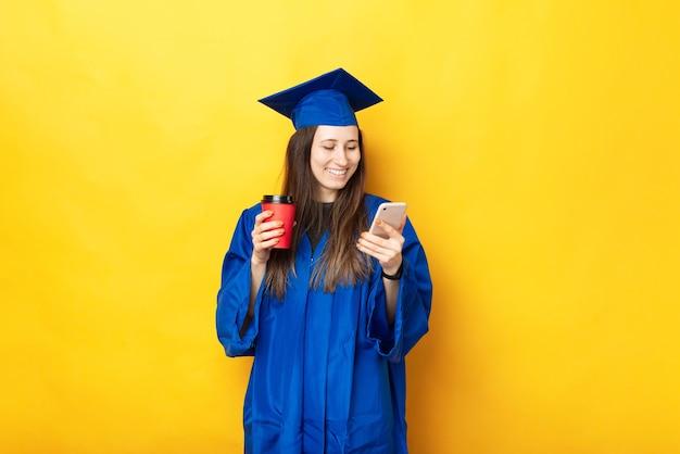 Foto de uma jovem sorridente se formando, usando o smartphone e segurando uma xícara de café