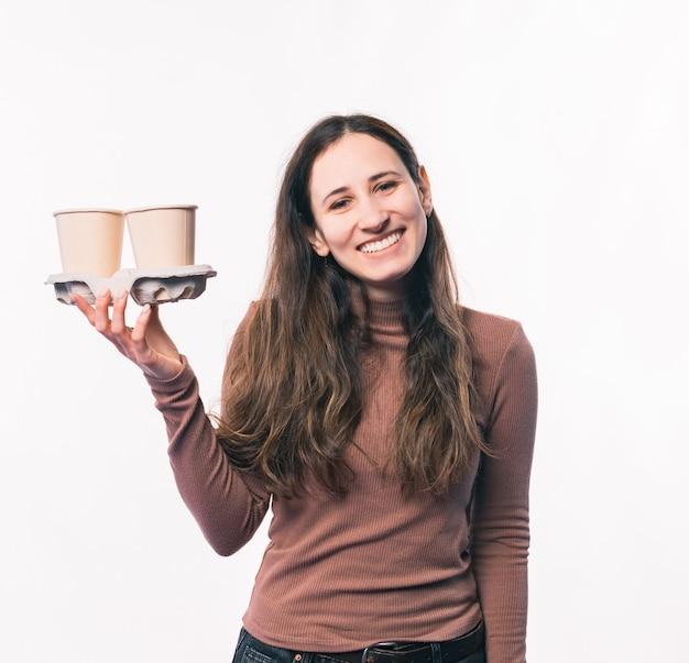 Foto de uma jovem sorridente segurando duas xícaras de café para viagem