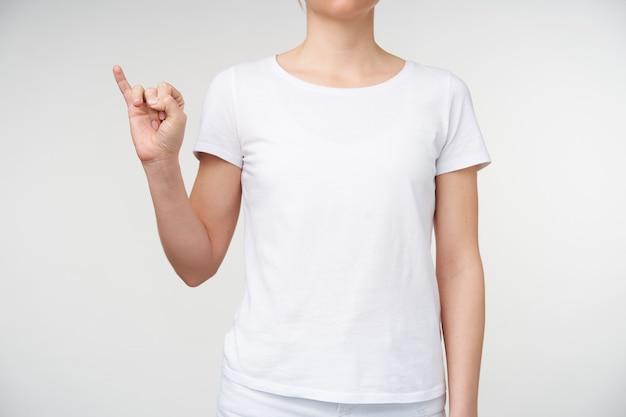 Foto de uma jovem vestida com roupas casuais, mantendo o dedo mínimo levantado enquanto aponta a letra i na linguagem de sinais, sendo isolada sobre um fundo branco