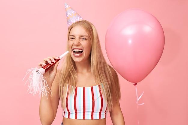 Foto de uma linda adolescente linda com cabelo loiro solto e aparelho dental posando em rosa com soprador de festa e balão de hélio, rindo com a boca aberta