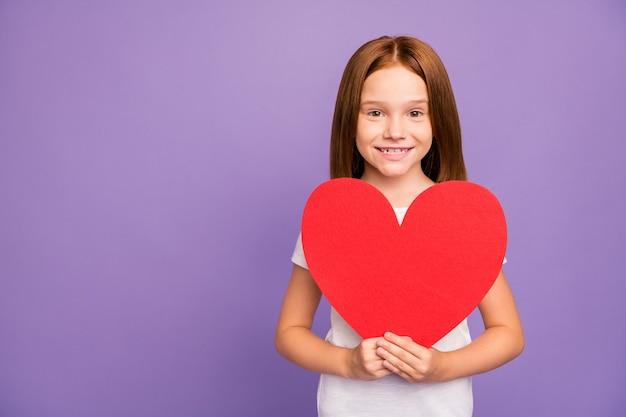 Foto de uma linda criança ruiva segurando um grande coração de papel vermelho
