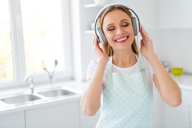 Foto de uma linda dona de casa passando a manhã de fim de semana ouvindo música usando fones de ouvido modernos e legais, uma melodia agradável obtendo energia para limpeza geral de cozinha branca