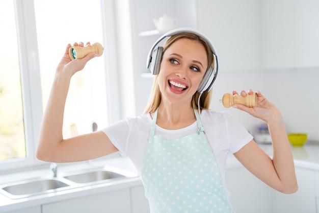 Foto de uma linda dona de casa passando a manhã ouvindo música com fones de ouvido modernos e legais curtindo a melodia segurando recipientes de pimenta na cozinha branca dentro de casa