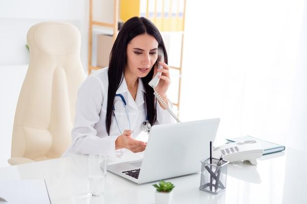 Foto de uma linda doutora falando por telefone, consultando paciente, tela, laptop