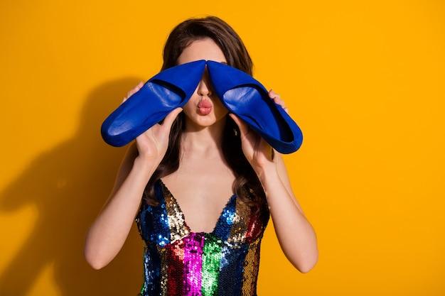 Foto de uma linda garota bonita fechando a tampa, olhos, rosto com sapatos novos, comprar sapatos estiletes enviar beijo no ar, usar saia arco-íris isolada sobre fundo de cor de brilho brilhante