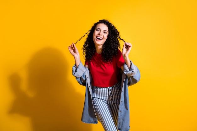 Foto de uma linda garota brincando de cachos se divertindo, vestindo uma camiseta vermelha com uma jaqueta jeans listrada isolada de fundo de cor amarela