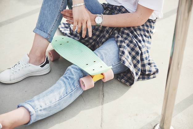 Foto de uma linda garota com cabelos lindos segurando um skate em uma prancha longa