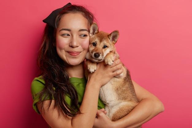 Foto de uma linda garota coreana apaixonada por seu cachorro shiba inu, abraça o animal de estimação com um sorriso, tem cabelo escuro, usa uma camiseta verde, posa com um animal contra um fundo rosa.