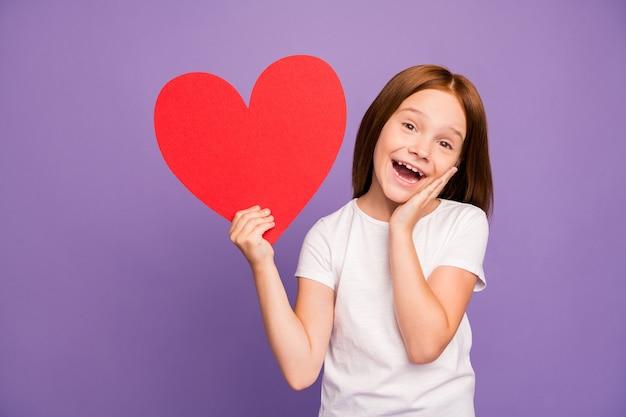 Foto de uma linda garota ruiva segurando um grande coração de papel vermelho