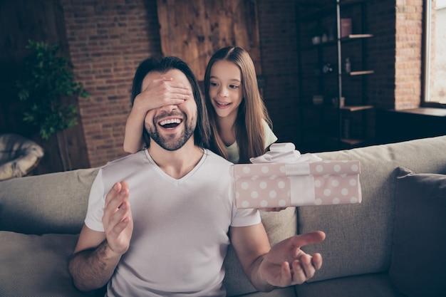 Foto de uma linda garotinha adorável e um jovem papai sentado no sofá confortável
