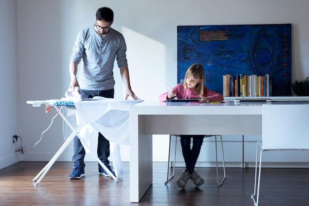 Foto de uma linda garotinha desenhando no caderno enquanto o pai dela passava uma camisa em casa.