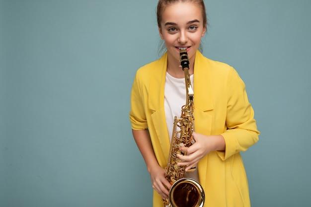 Foto de uma linda garotinha morena feliz e sorridente, vestindo uma elegante jaqueta amarela, isolada sobre uma parede de fundo azul tocando saxofone, olhando para a câmera