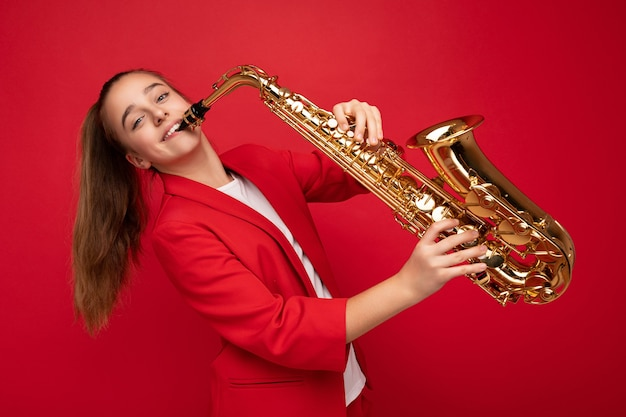 Foto de uma linda garotinha morena feliz e sorridente, vestindo uma elegante jaqueta vermelha, isolada sobre a parede de fundo vermelho tocando saxofone, olhando para a câmera