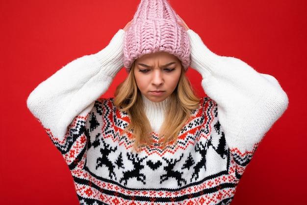 Foto de uma linda jovem loira chateada com raiva isolada sobre a parede de fundo vermelho, vestindo uma camisola de inverno e um chapéu rosa, olhando para baixo.