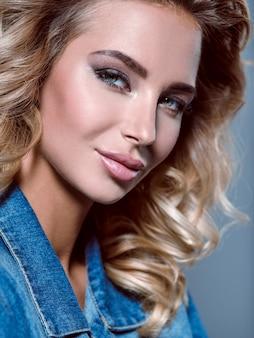 Foto de uma linda jovem loira com cabelo encaracolado. closeup rosto atraente e sensual de mulher branca com cabelo comprido. maquilhagem de olhos esfumados.