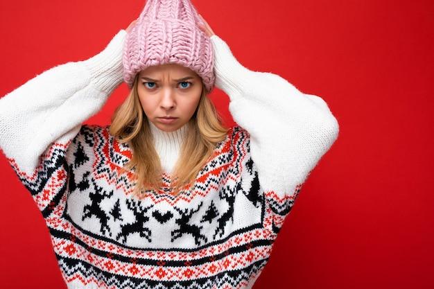 Foto de uma linda jovem loira triste insatisfeita isolada sobre a parede de fundo vermelho, vestindo uma camisola de inverno e um chapéu rosa, olhando para a câmera.