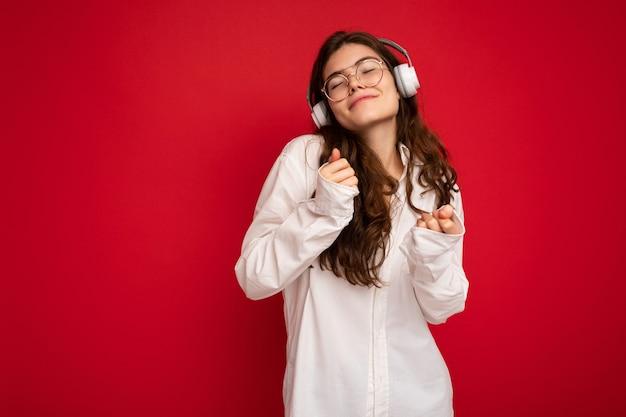 Foto de uma linda jovem morena sorridente feliz vestindo camisa branca e óculos ópticos