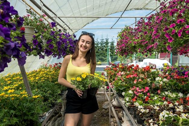 Foto de uma linda jovem posando entre flores em uma estufa