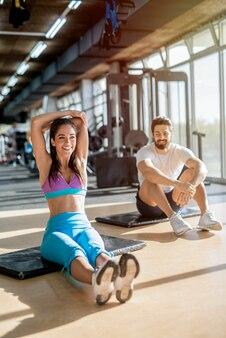 Foto de uma linda jovem sorridente desportiva, esticando os músculos do braço após o treino, enquanto seu treinador pessoal de fitness a está observando.