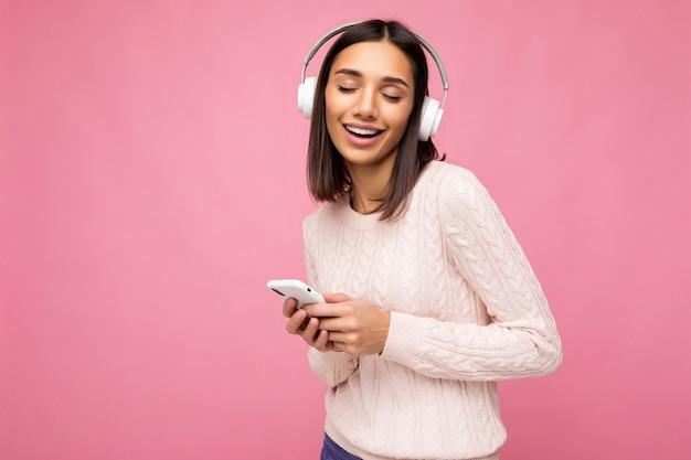 Foto de uma linda jovem sorridente e alegre, vestindo uma roupa casual elegante isolada
