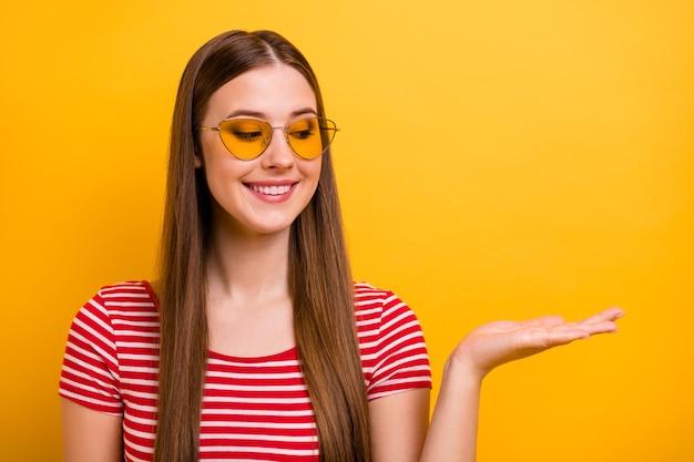Foto de uma linda jovem sorridente, segurando a mão, olhando o espaço vazio, escolhendo a melhor variante, aconselhando objeto, usar óculos de sol, camisa vermelha branca listrada fundo de cor amarela vibrante