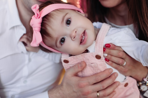 Foto de uma linda menina com uma fita rosa na cabeça e um laço olhando curiosamente para a frente