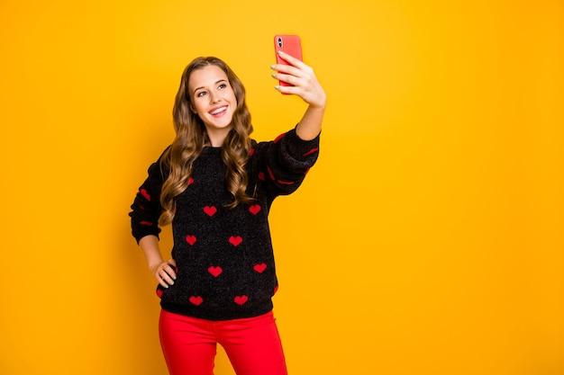 Foto de uma linda moça de mãos dadas com o telefone fazendo selfies enérgicos positivos e engraçados usando calças vermelhas de pulôver com padrão de corações