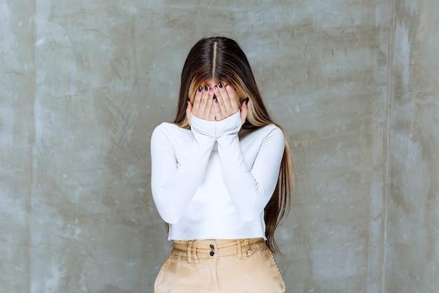 Foto de uma linda modelo de garota em pé e fechando o rosto com as mãos