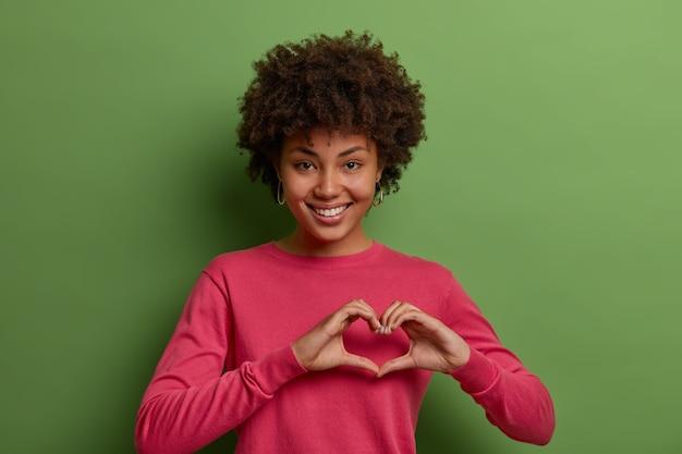 Foto de uma linda mulher afro-americana expressando amor, estando em um clima romântico, mostra o sinal do coração, confessa sentimentos verdadeiros, tem simpatia, vestida com um macacão rosa, posa contra a parede verde