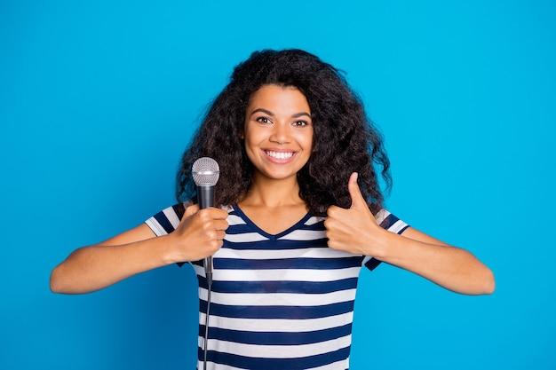 Foto de uma linda mulher bonita mostrando seu polegar segurando o microfone