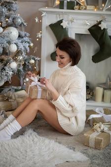 Foto de uma linda mulher branca abre uma caixa grande com um presente na atmosfera de ano novo