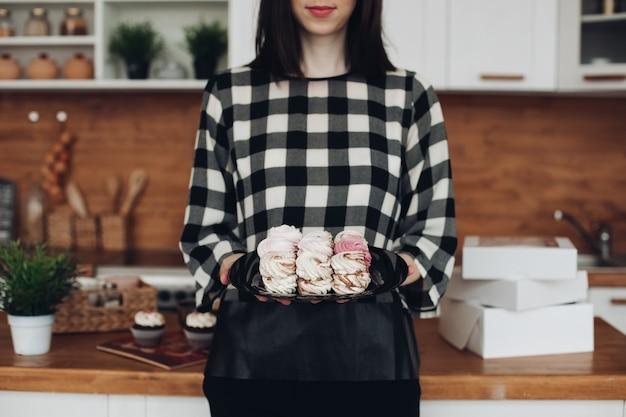 Foto de uma linda mulher branca com cabelo escuro curto em um suéter preto e branco segurando uma caixa com marshmallows