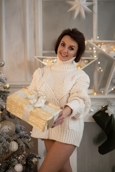 Foto de uma linda mulher branca segurando uma caixa grande com um presente e sorrisos