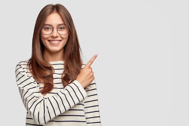 Foto de uma linda mulher caucasiana com expressão alegre, aponta com o dedo indicador para o espaço em branco da cópia, vestida com suéter listrado, mostra espaço livre no canto superior direito para sua promoção