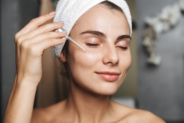 Foto de uma linda mulher com uma toalha na cabeça, aplicando óleo cosmético no rosto