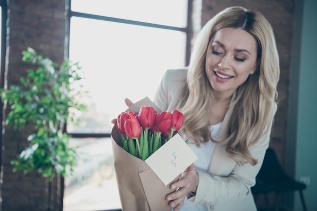 Foto de uma linda mulher de negócios chegando ao local de trabalho procurando tulipas frescas