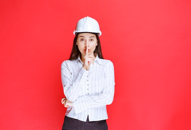 Foto de uma linda mulher de negócios com chapéu de segurança, fazendo sinal silencioso.