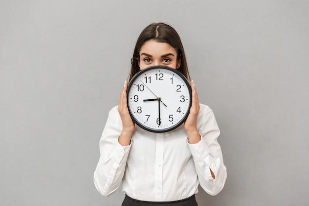 Foto de uma linda mulher de negócios com roupa formal, cobrindo o rosto com um grande relógio redondo, isolada sobre uma parede cinza