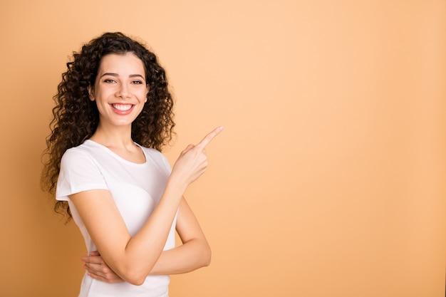 Foto de uma linda mulher de negócios indicando o dedo para o espaço vazio, oferta de preços de venda de compras, usar roupas casuais brancas isoladas fundo bege