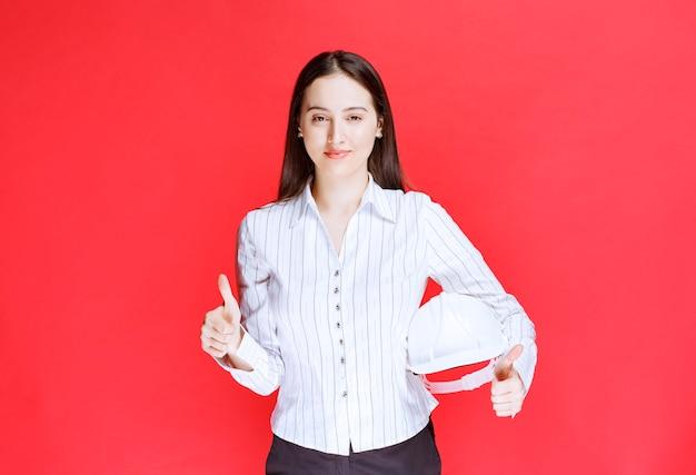 Foto de uma linda mulher de negócios segurando o chapéu de segurança e aparecendo um polegar.