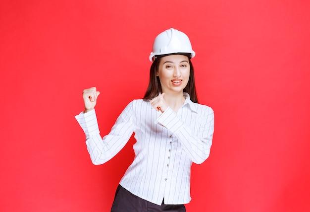 Foto de uma linda mulher de negócios usando chapéu de segurança, apontando para longe com os dedos.
