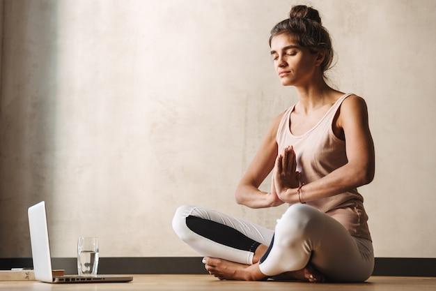 Foto de uma linda mulher em roupas esportivas meditando com gesto namastê e usando o laptop enquanto faz ioga no chão em casa