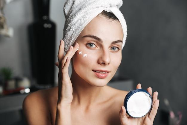 Foto de uma linda mulher enrolada em uma toalha aplicando creme no rosto