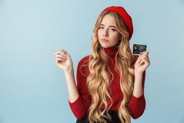 Foto de uma linda mulher loira de 20 anos usando boina vermelha segurando um cartão de crédito isolado