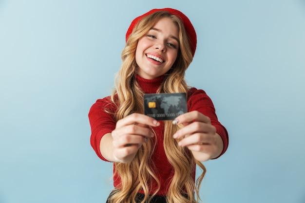 Foto de uma linda mulher loira de 20 anos usando uma boina vermelha segurando um cartão de crédito isolado