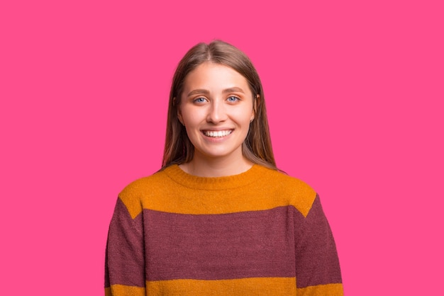 Foto de uma linda mulher loira está sorrindo sobre fundo rosa.